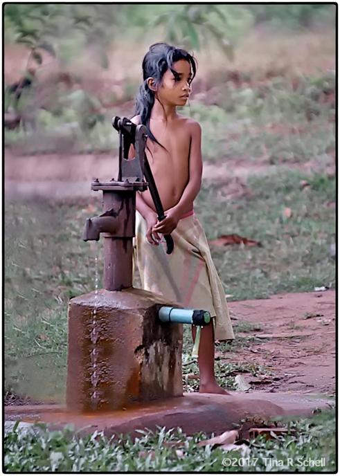 GIRL AT THE PUMP, CAMBODIA